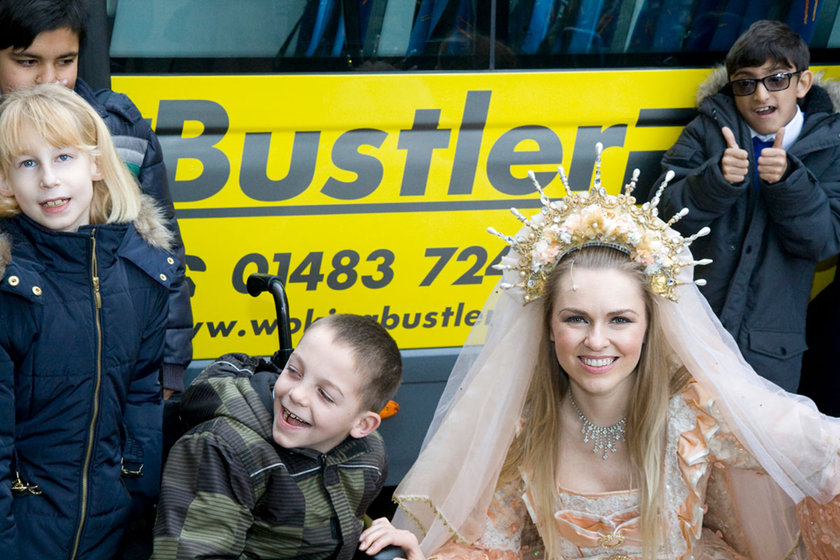 Panto character with children with a Bustler bus